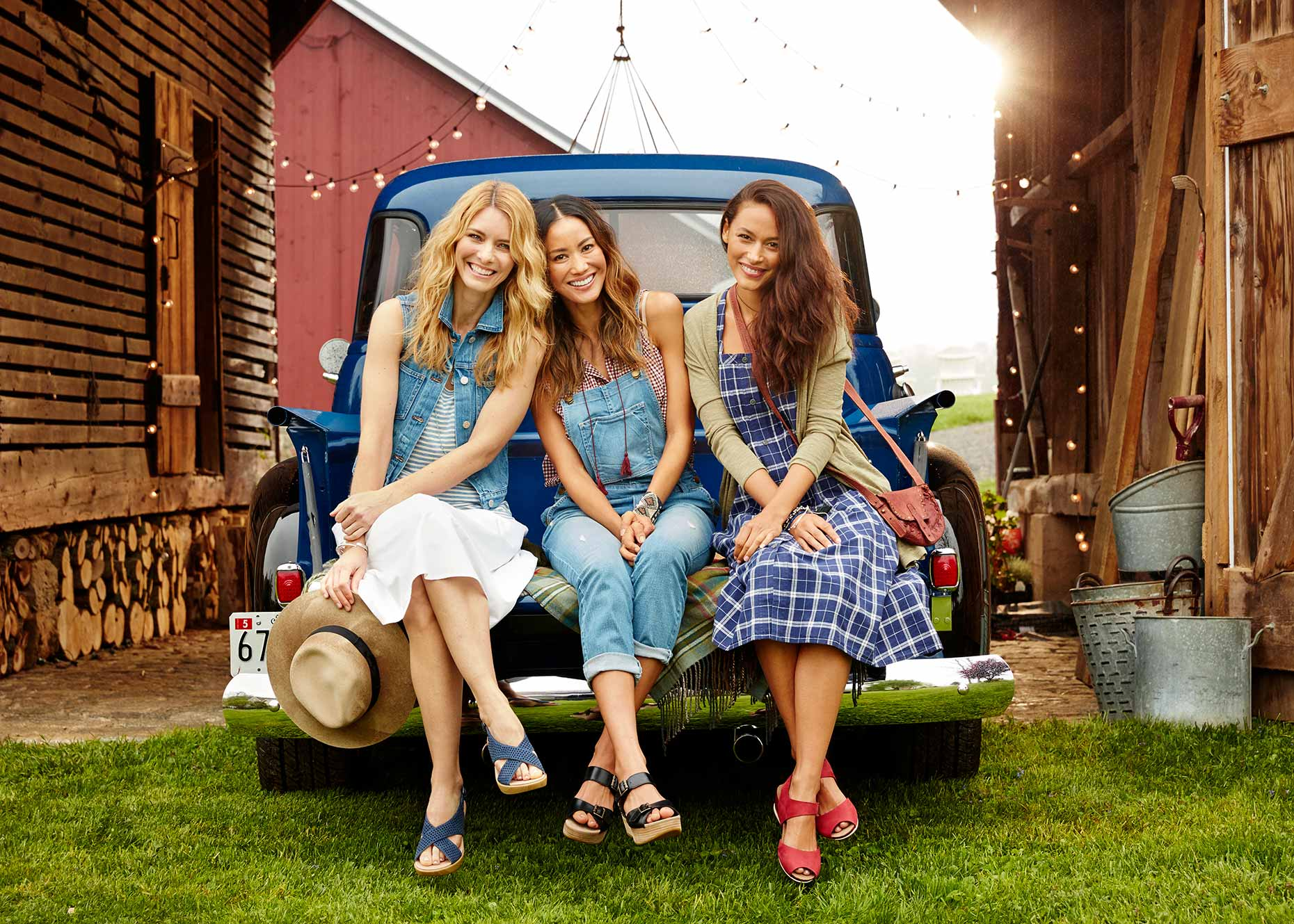 3 women hang out in the back of an old pickup truck