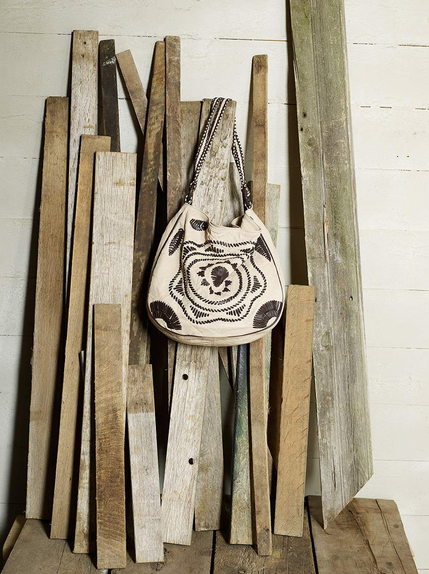 Leather handbag hung against raw wooden planks