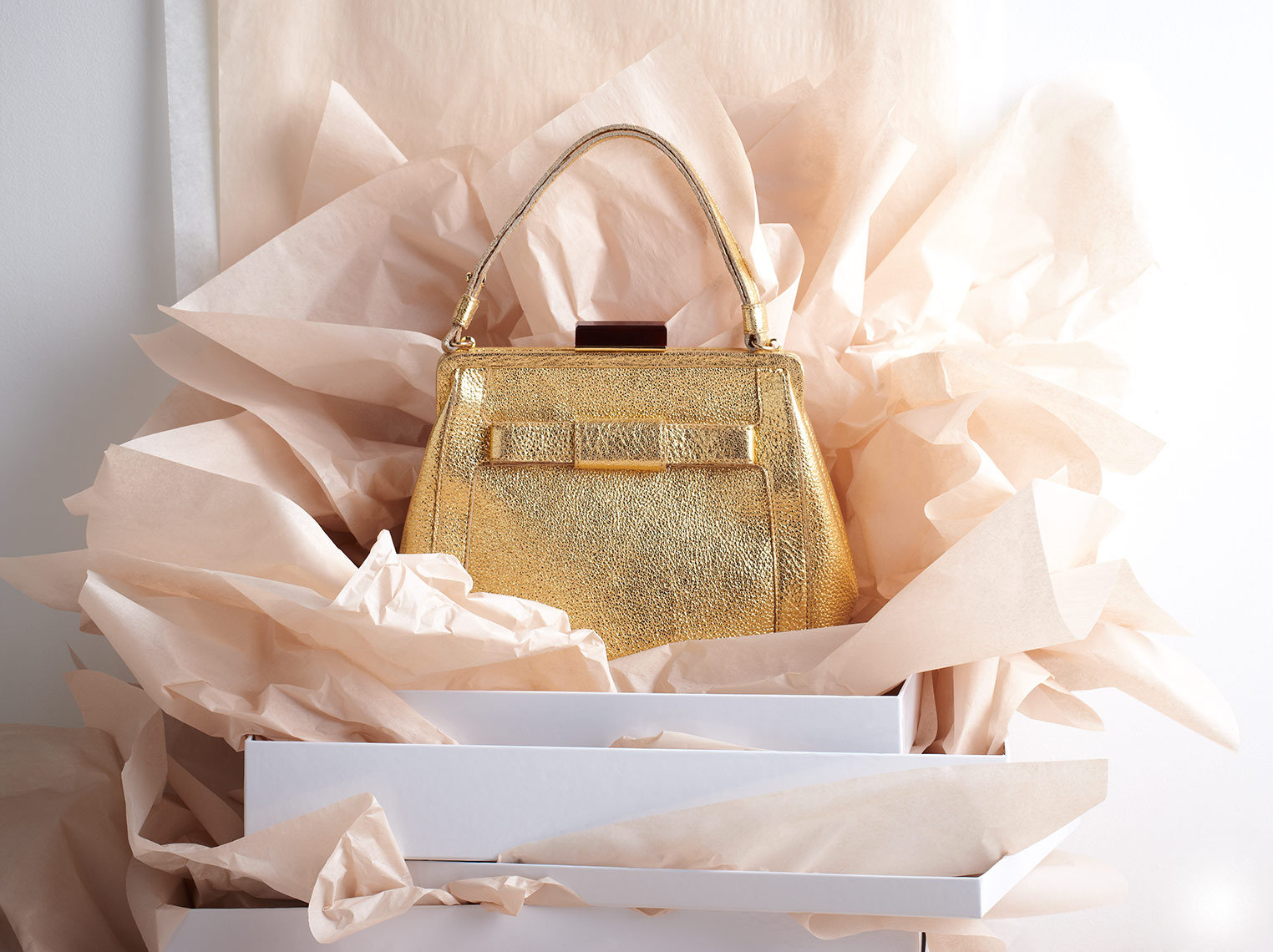 Gold shiny handbag with pink tissue paper.