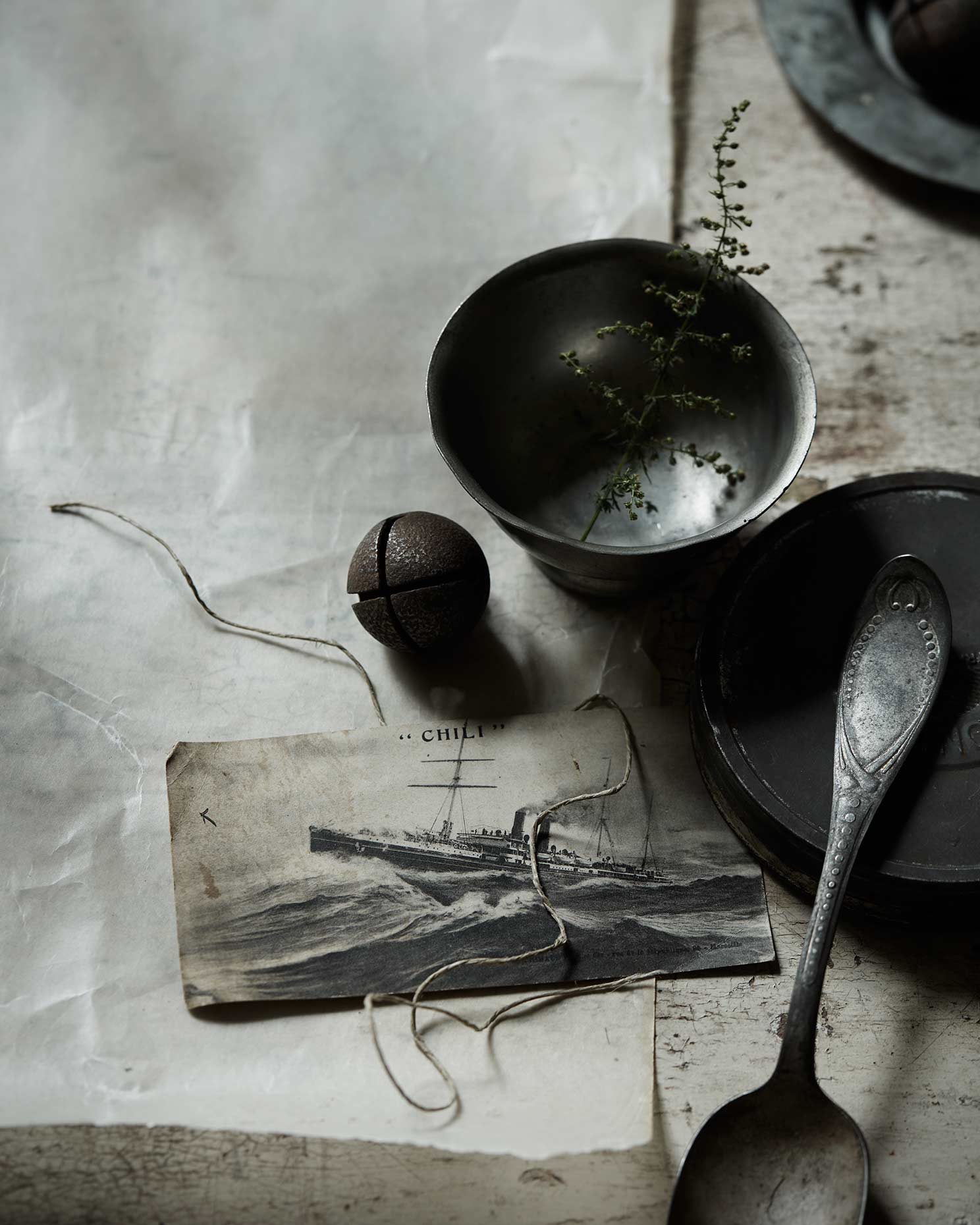 Artistic dark still life photograph with postcard and kitchen items