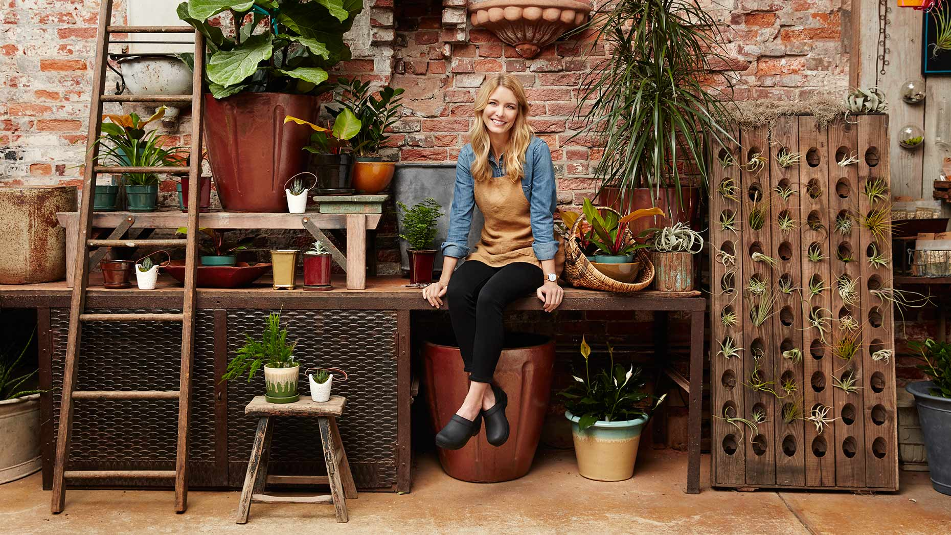 A shop owner proudly poses for a picture in her plant store