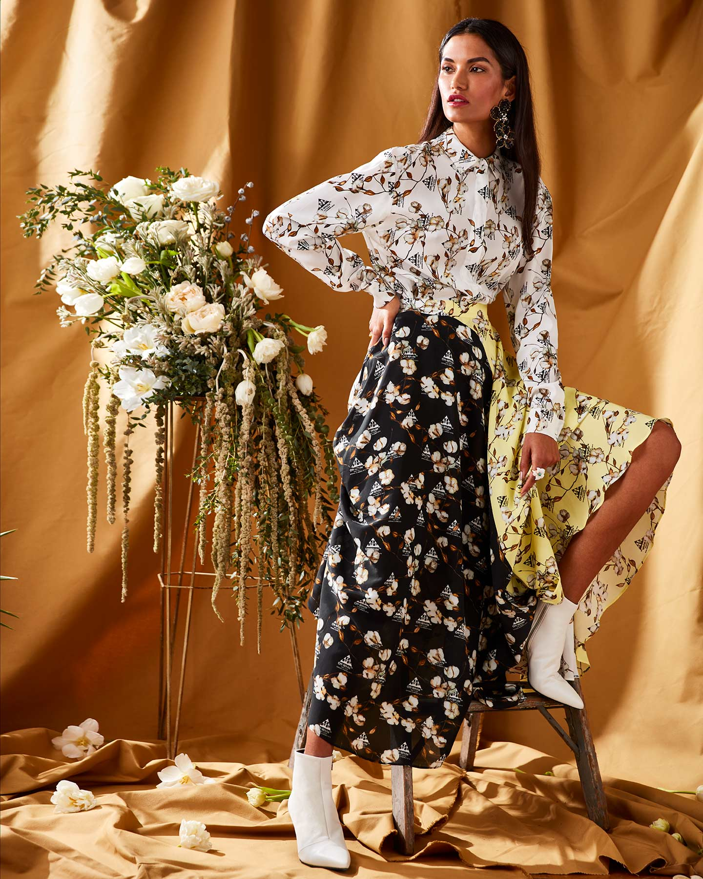 Fashion photography featuring a model and large floral arrangement against a yellow background