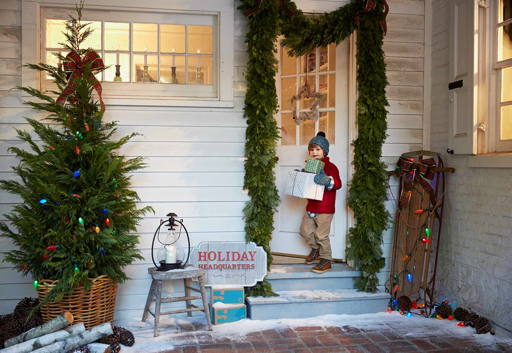 A young boy and his Christmas presents enters his house