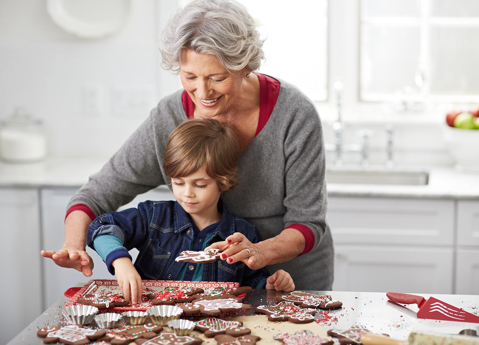 A grandma and her grandson baking cookies in the kitchen