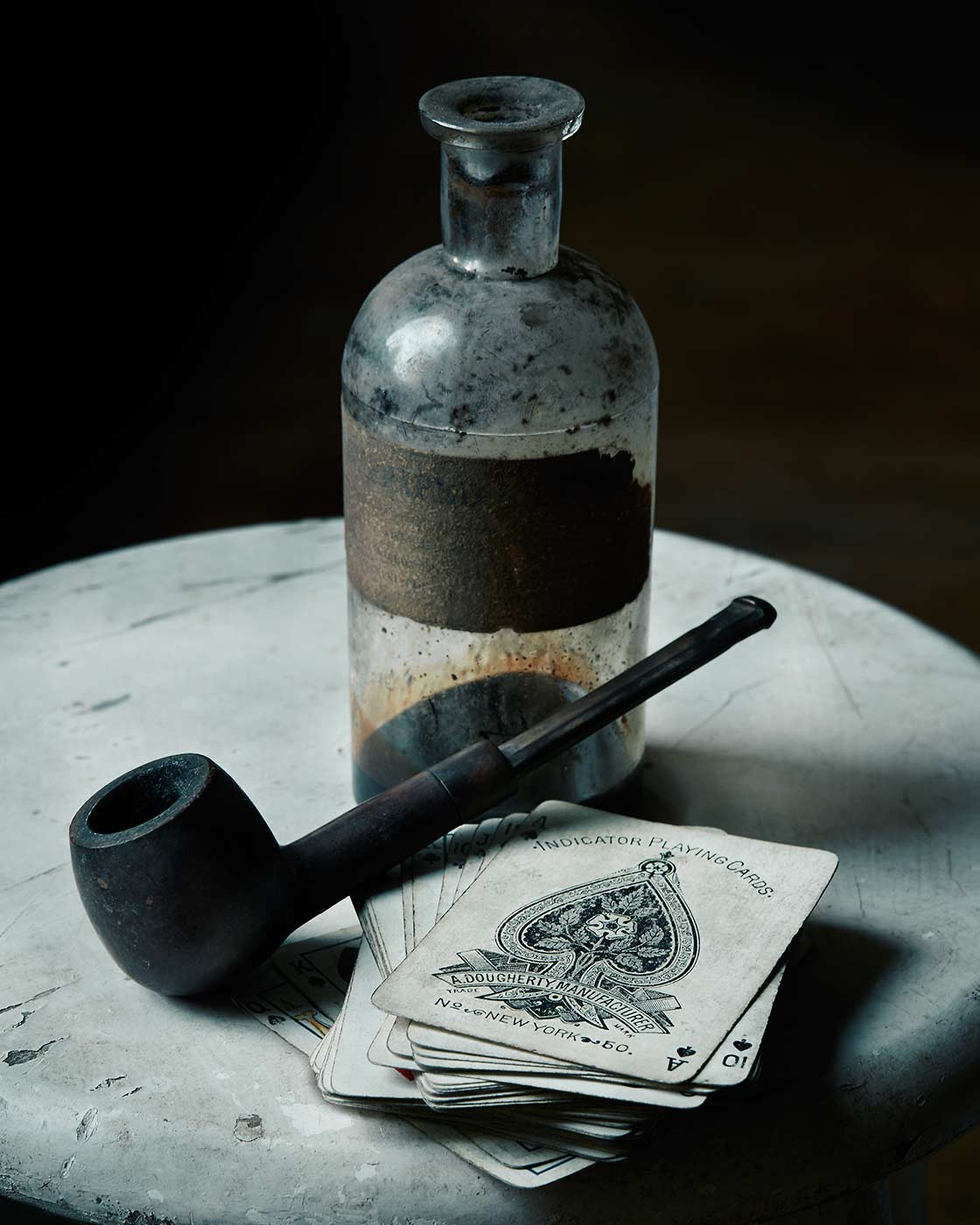 Dark still life photo with cards and pipe.