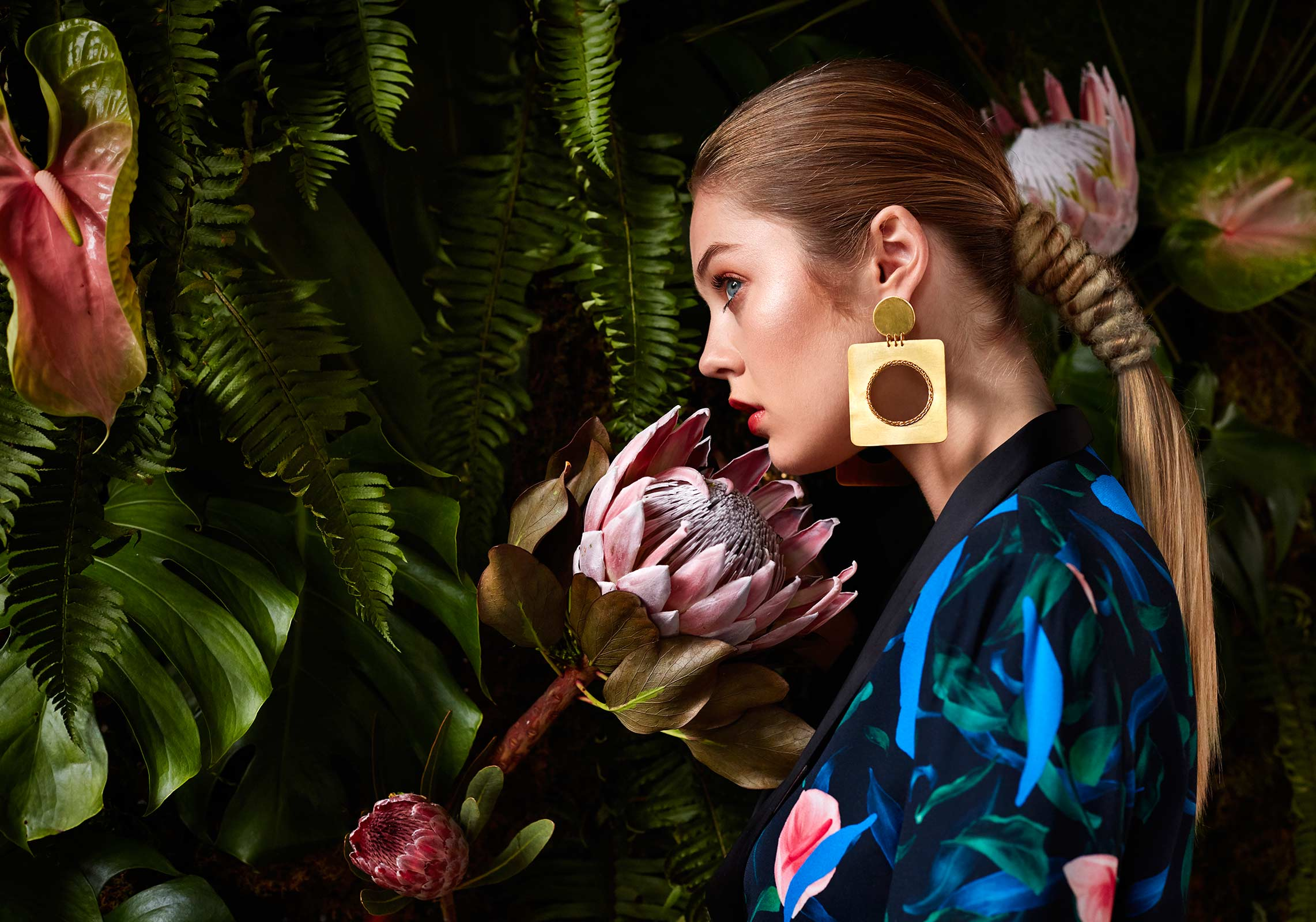 Colorful fashion photograph of model against a large flower wall.
