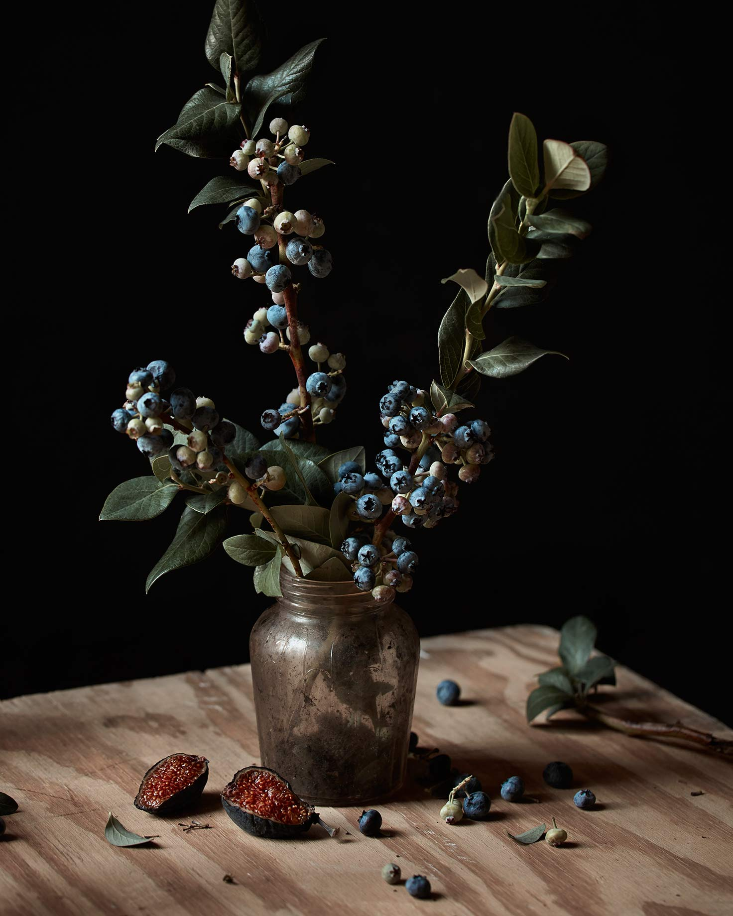 Blueberry bush branch in vase on tabletop.