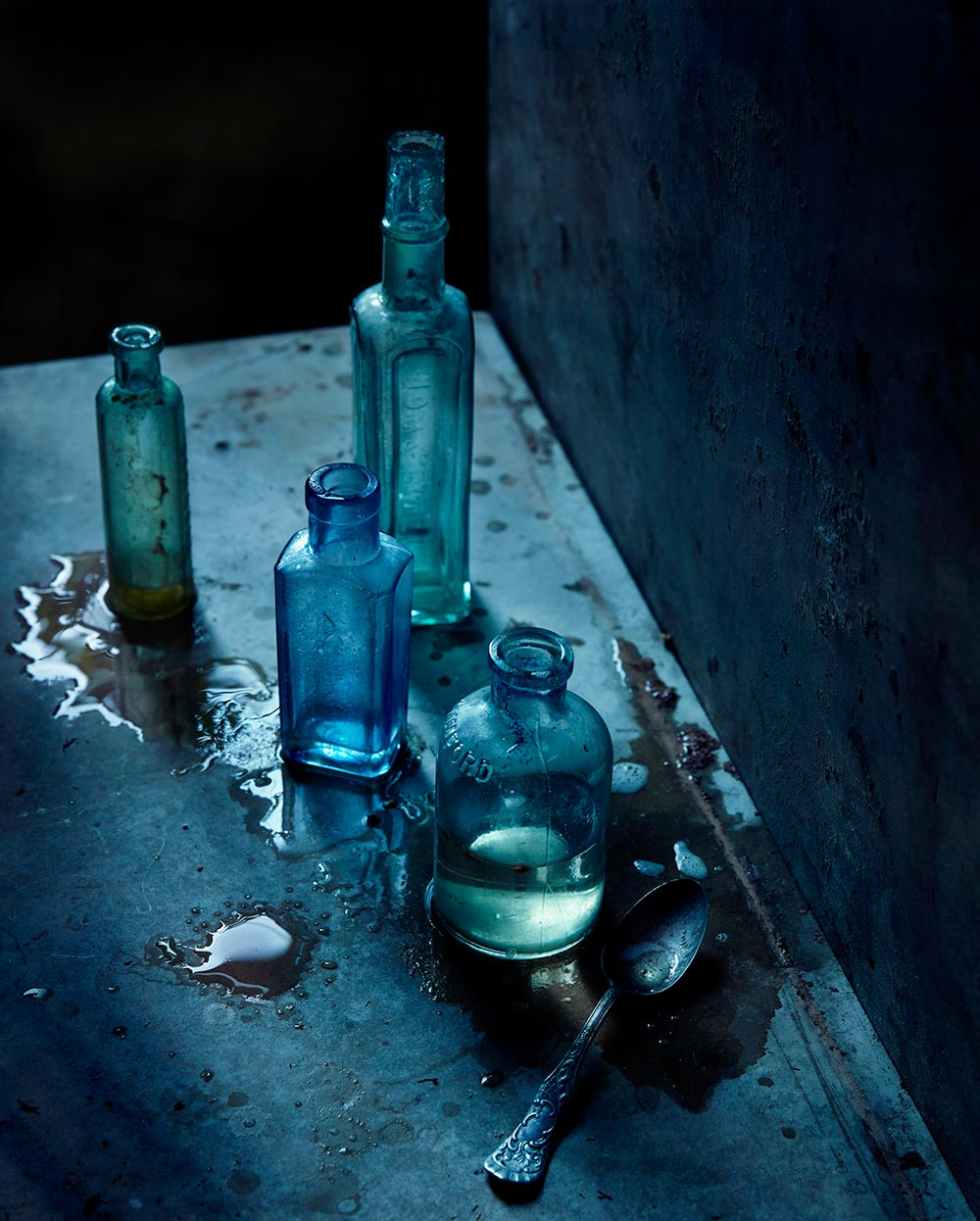Dark moody still life photograph of glass bottles on a concrete background