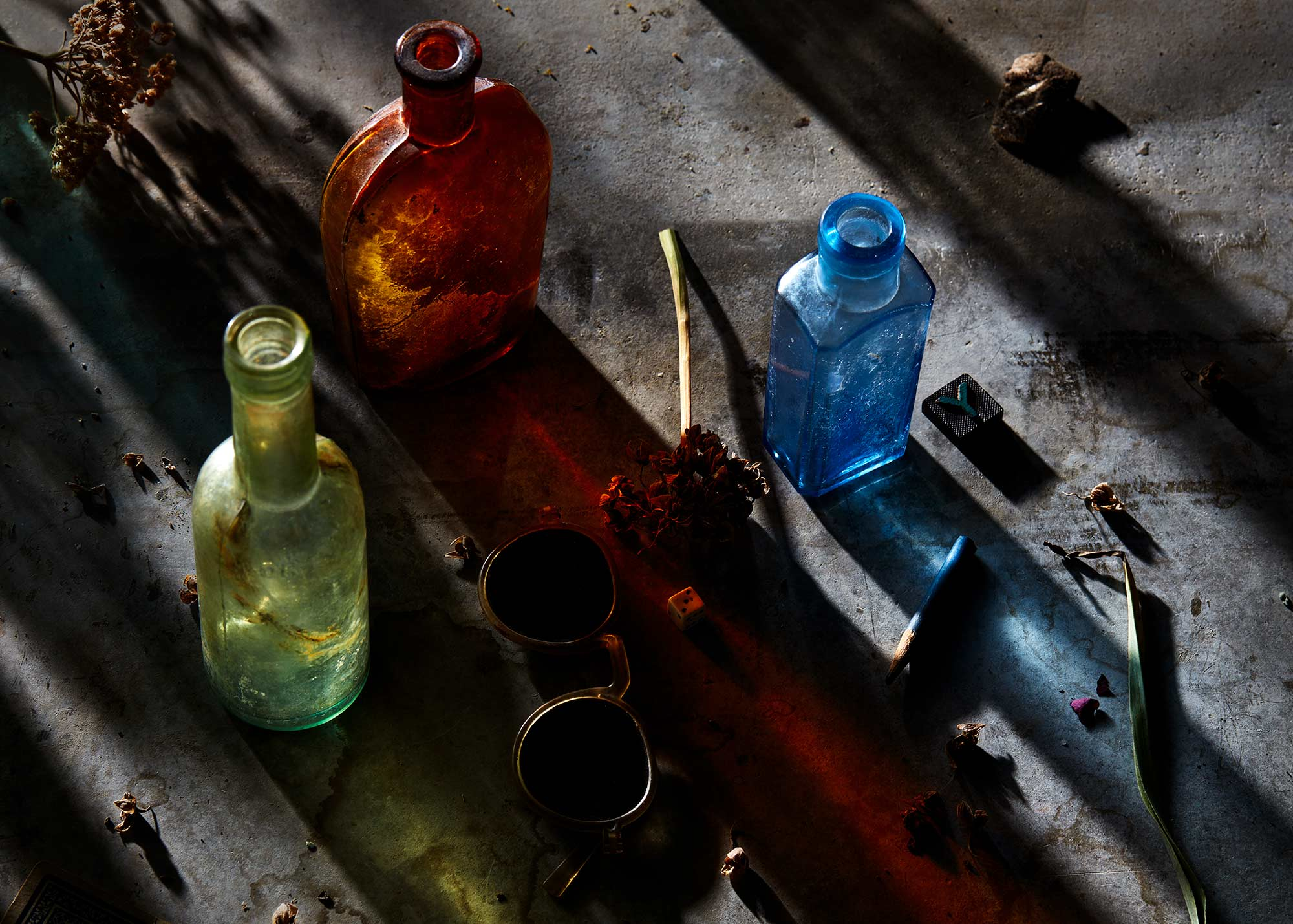 still life photograph of colorful bottles and shadows