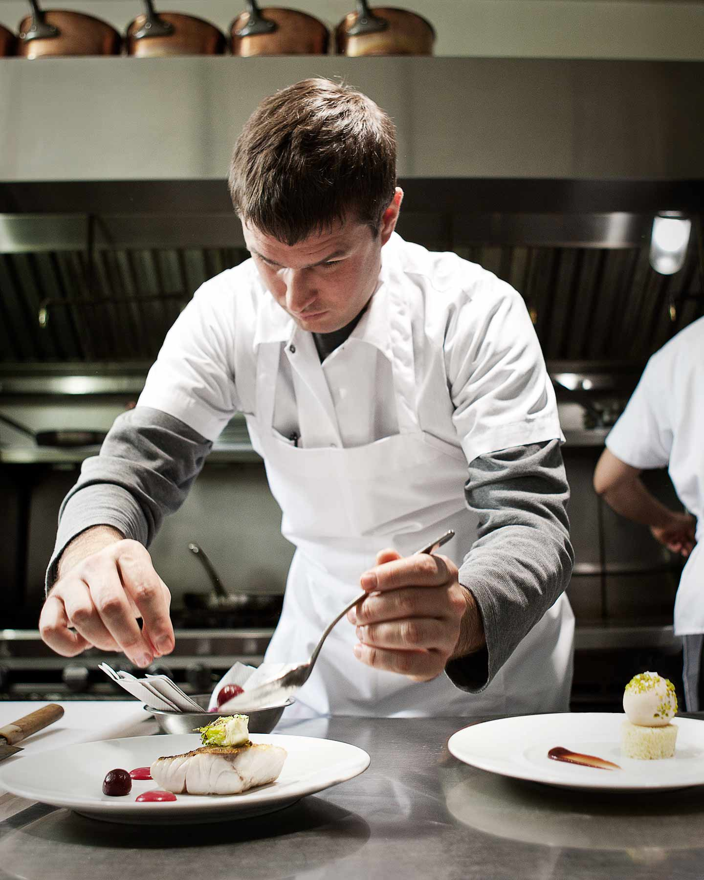 chef concentrating on plating a dish at his restaurant