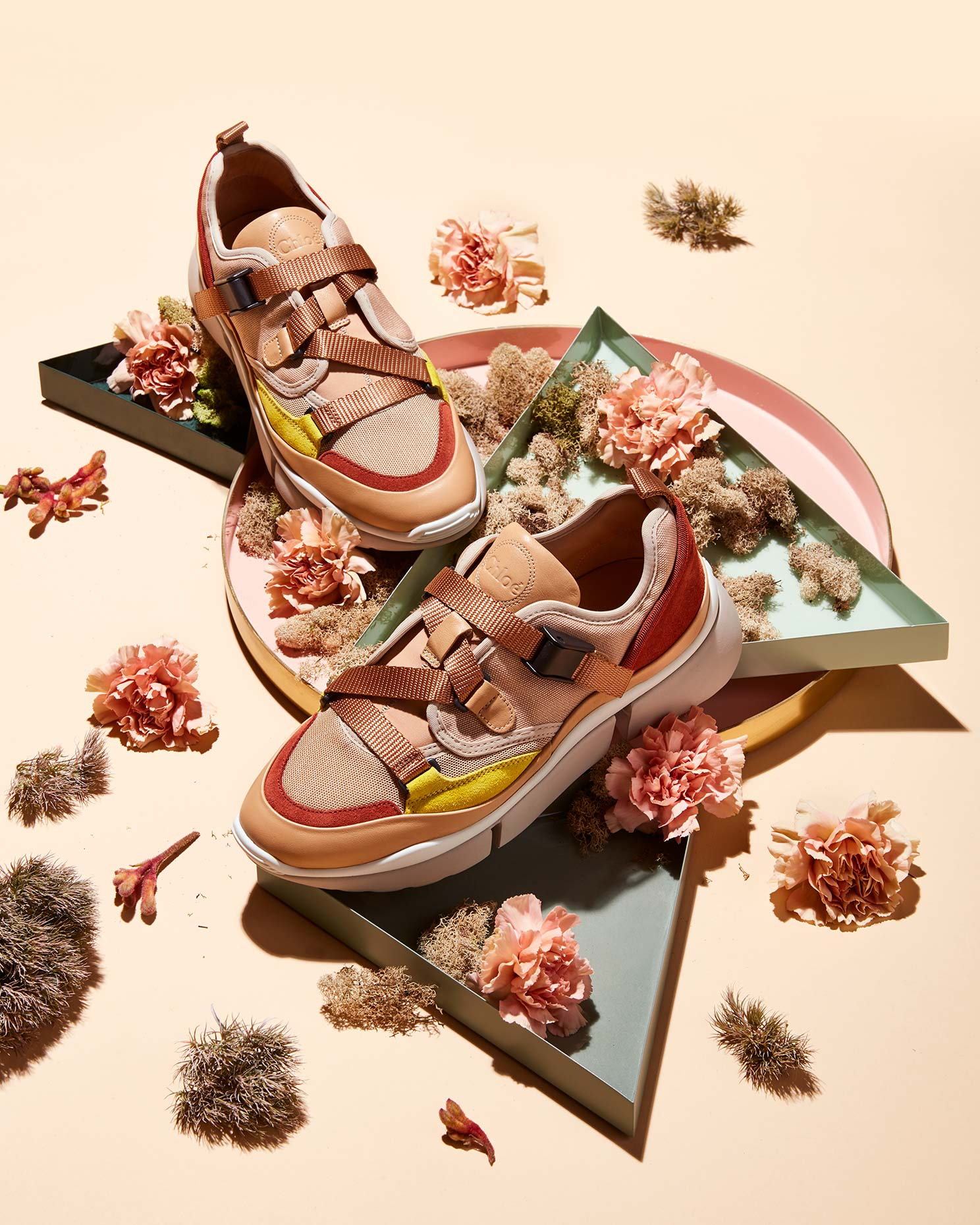 fashion still life photo of pink chloe sneakers and flowers