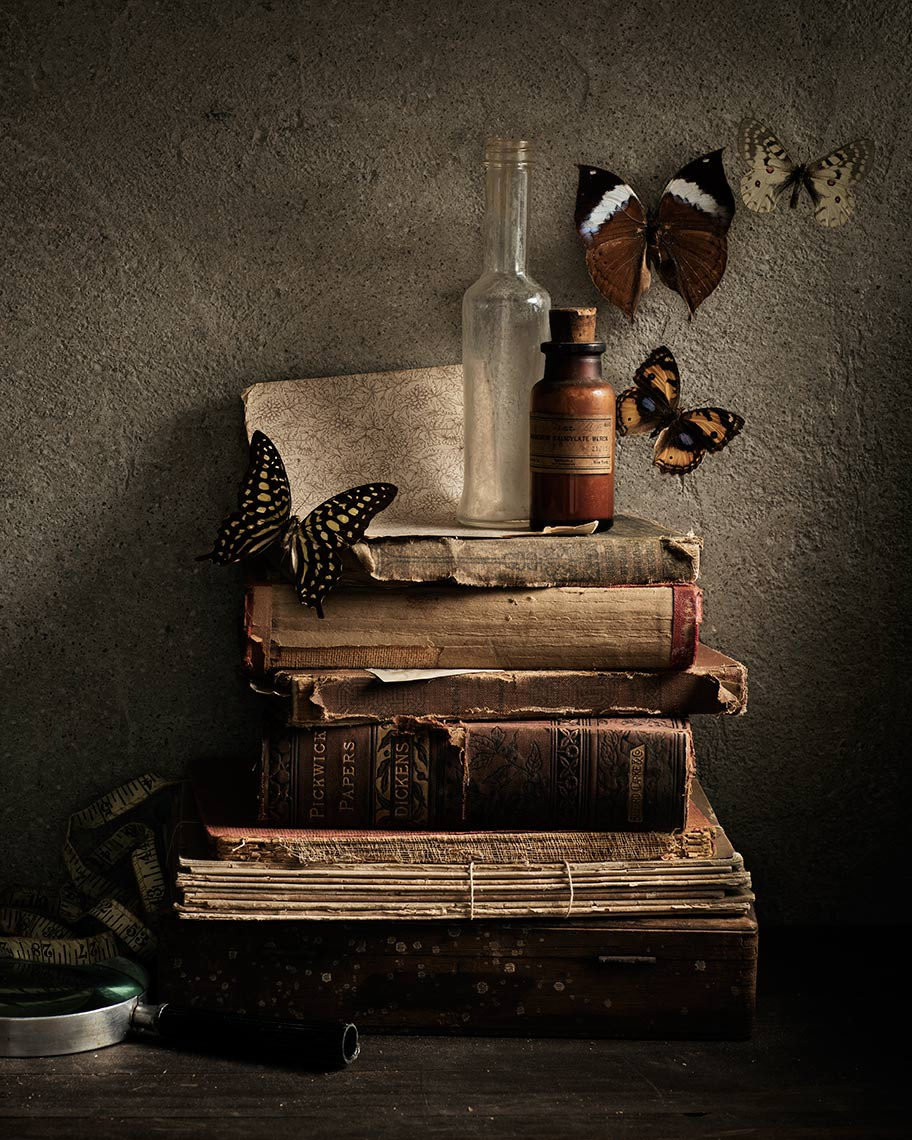 Vintage books with colorful floating butteries on a dark rustic background.