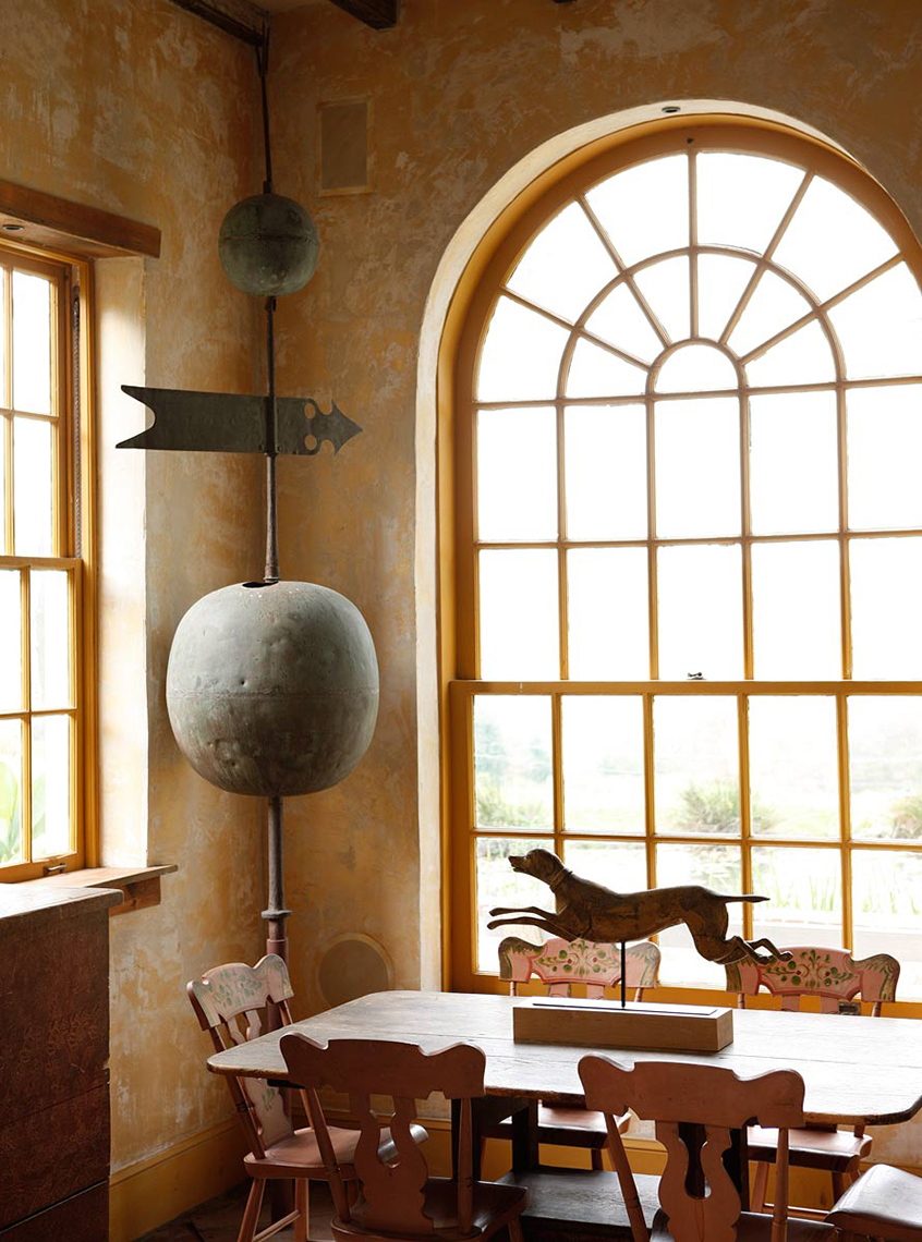 Large window and cozy chair shown in an old farmhouse