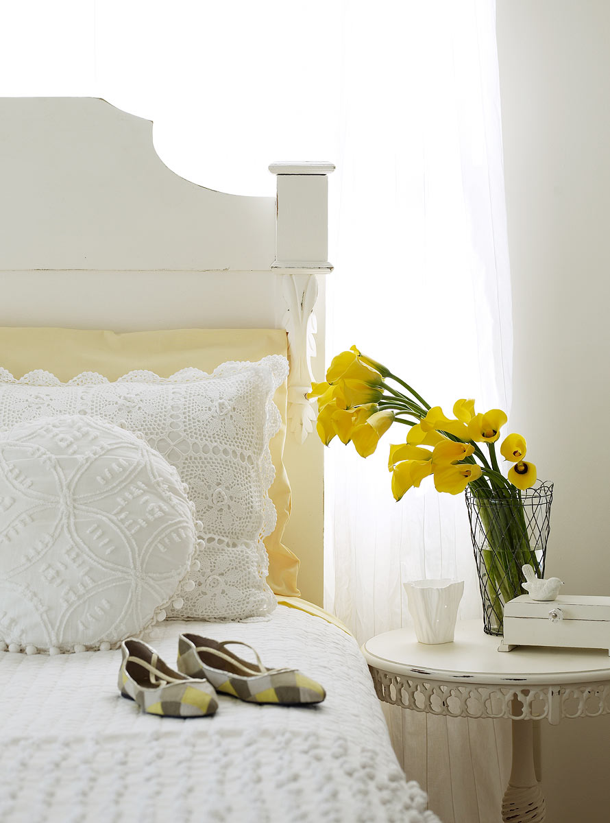 Bedroom scene with yellow shoes on the bed and flowers
