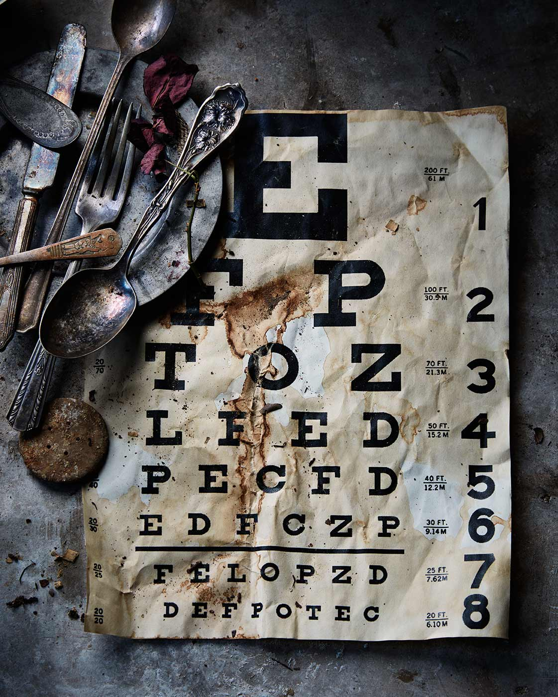 Dark moody still life photograph featuring an eye chart and silverware.