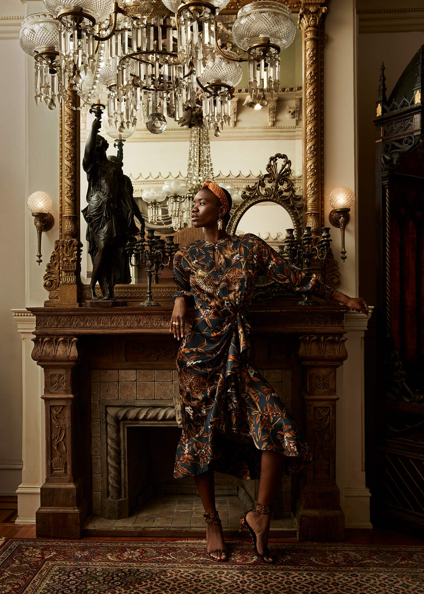 Fashion photograph of a model wearing animal print dress in front of a mirror
