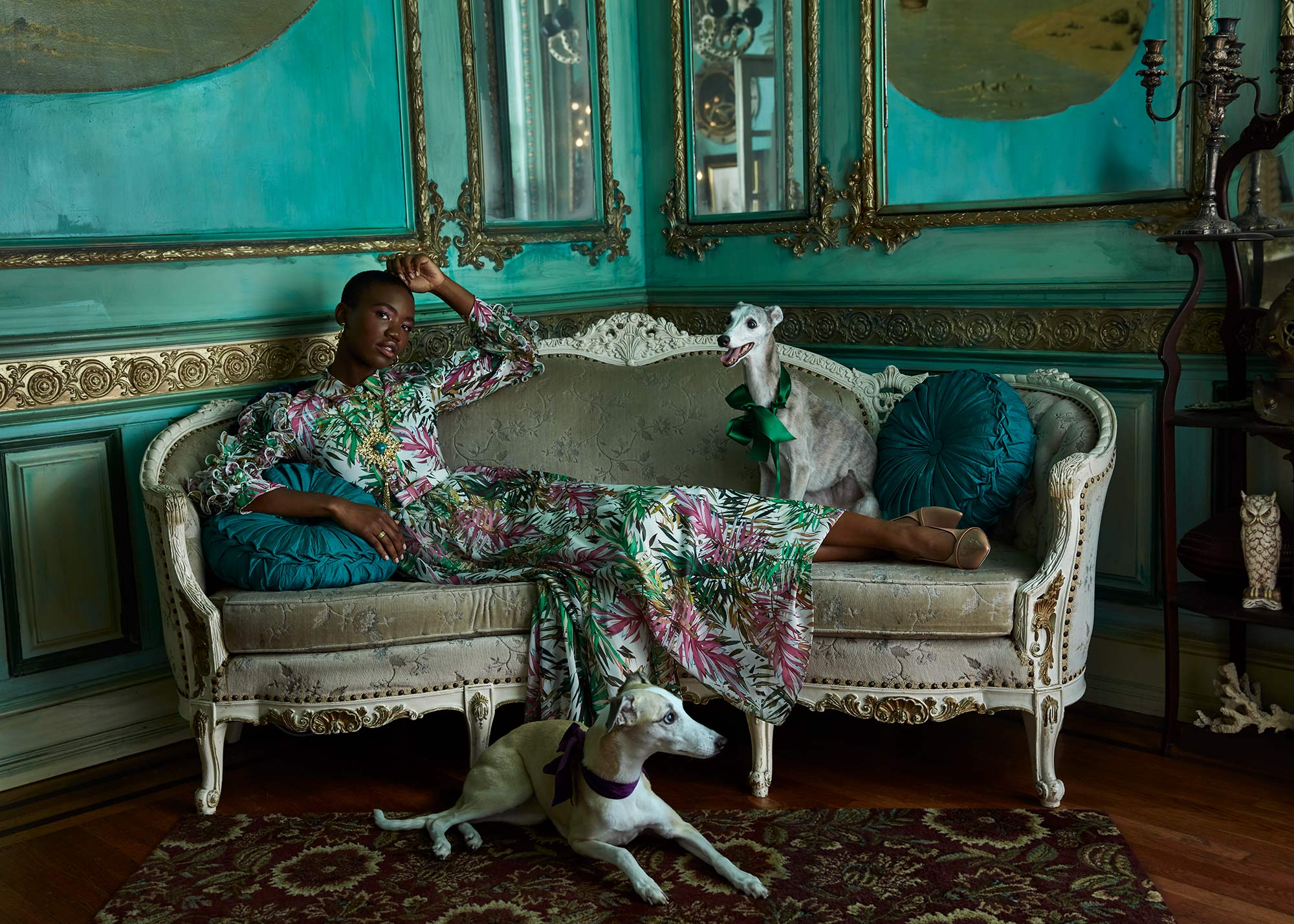 Fashion photograph of a model lounging on a couch with two dogs