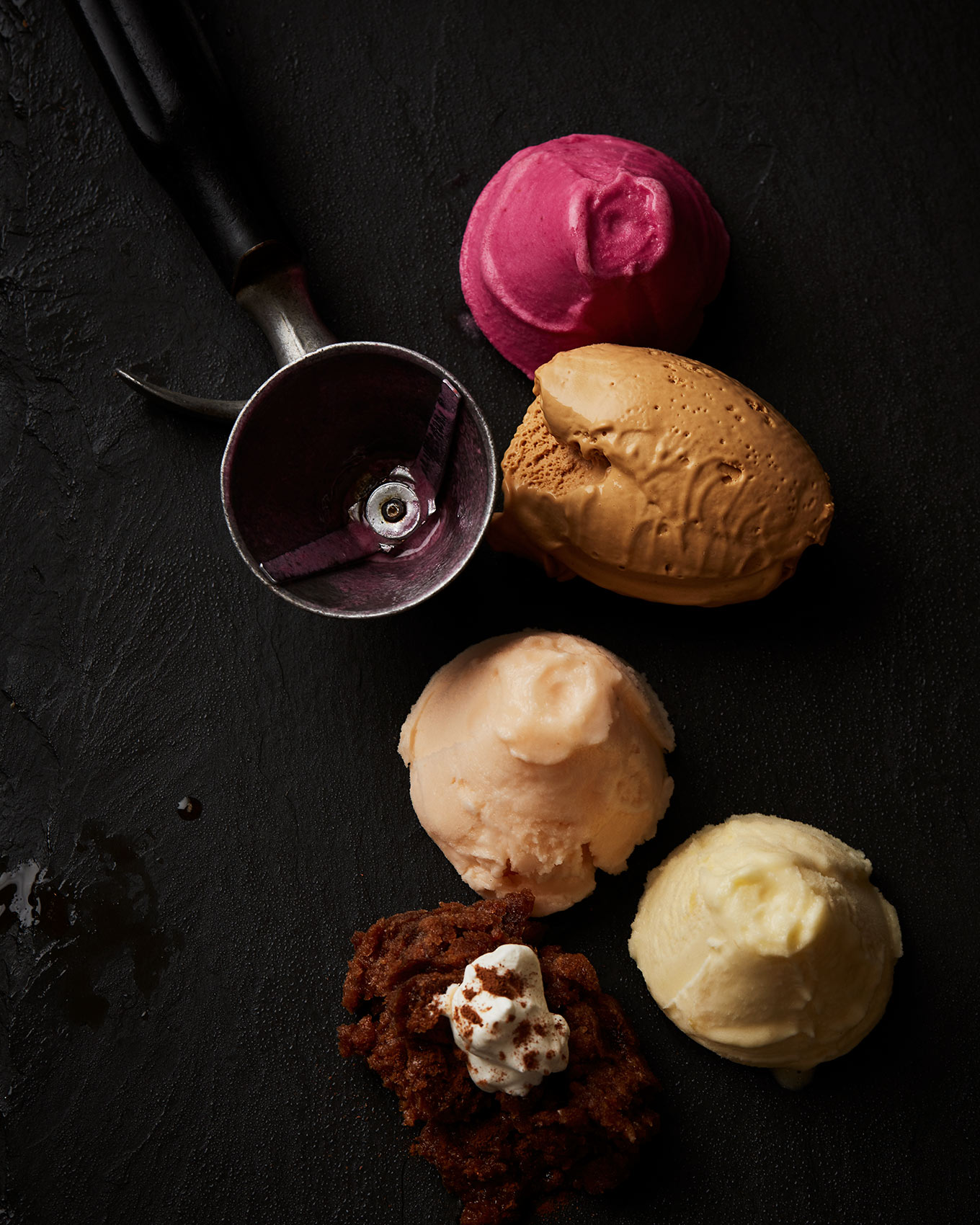 Scoops of colorful ice cream on a black slate background