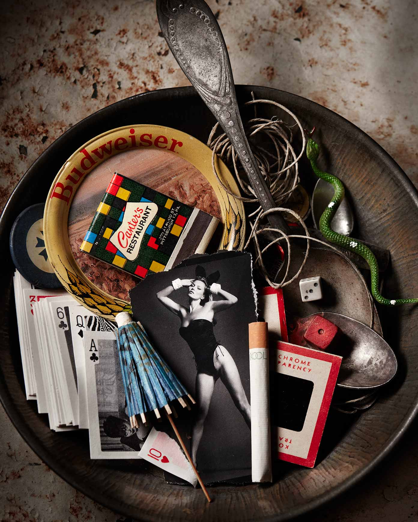 Still life photograph of a bowl with junk and Kate Moss.