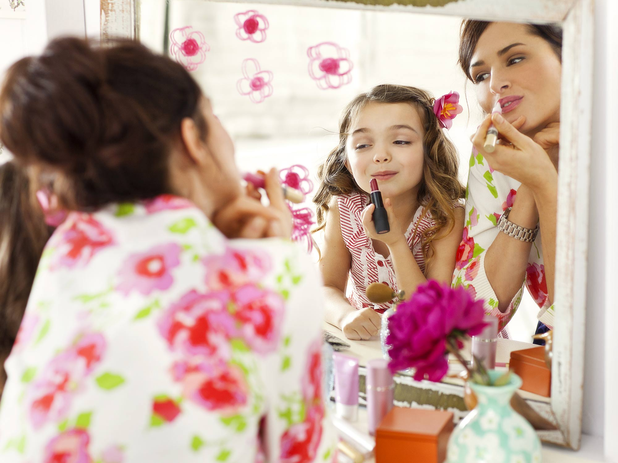A mom and her daughter play with makeup in a mirror