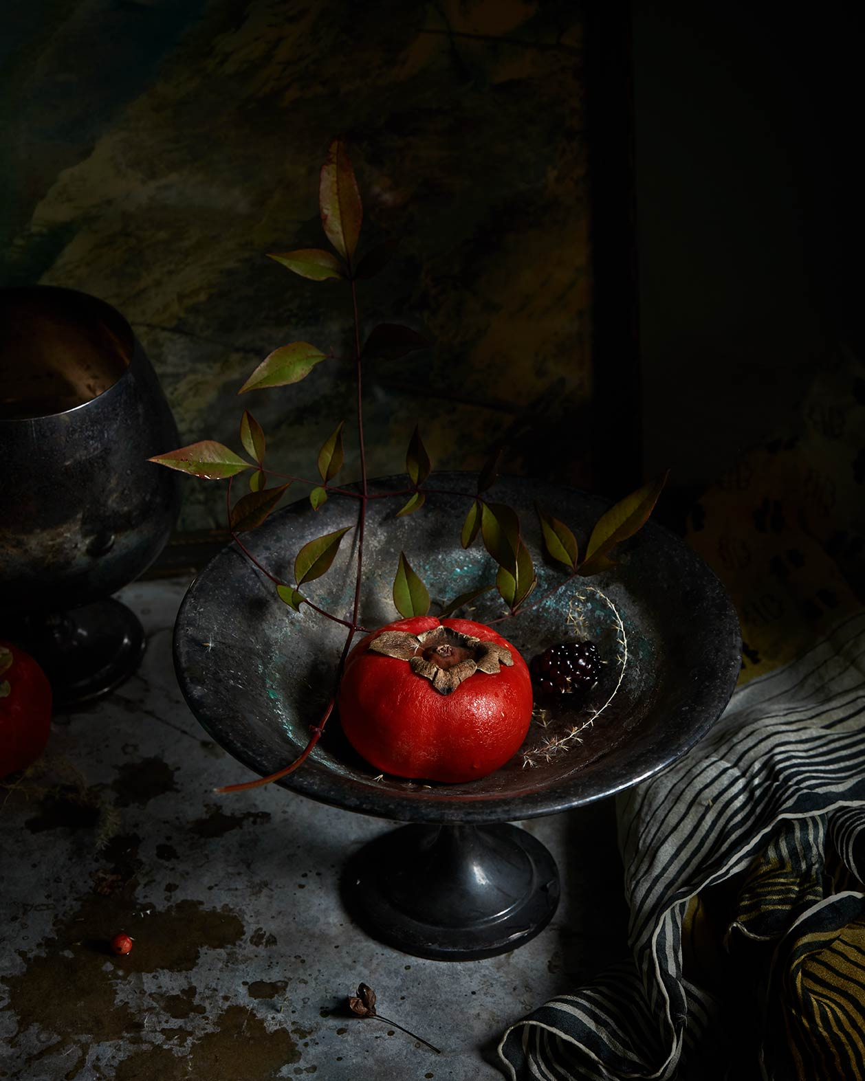 Dark still life photograph featuring fruit and old props.