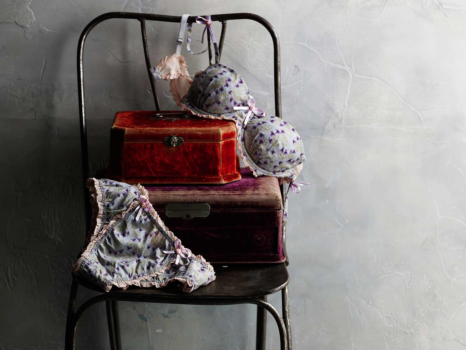 Undergarments on chair with vintage suitcases.