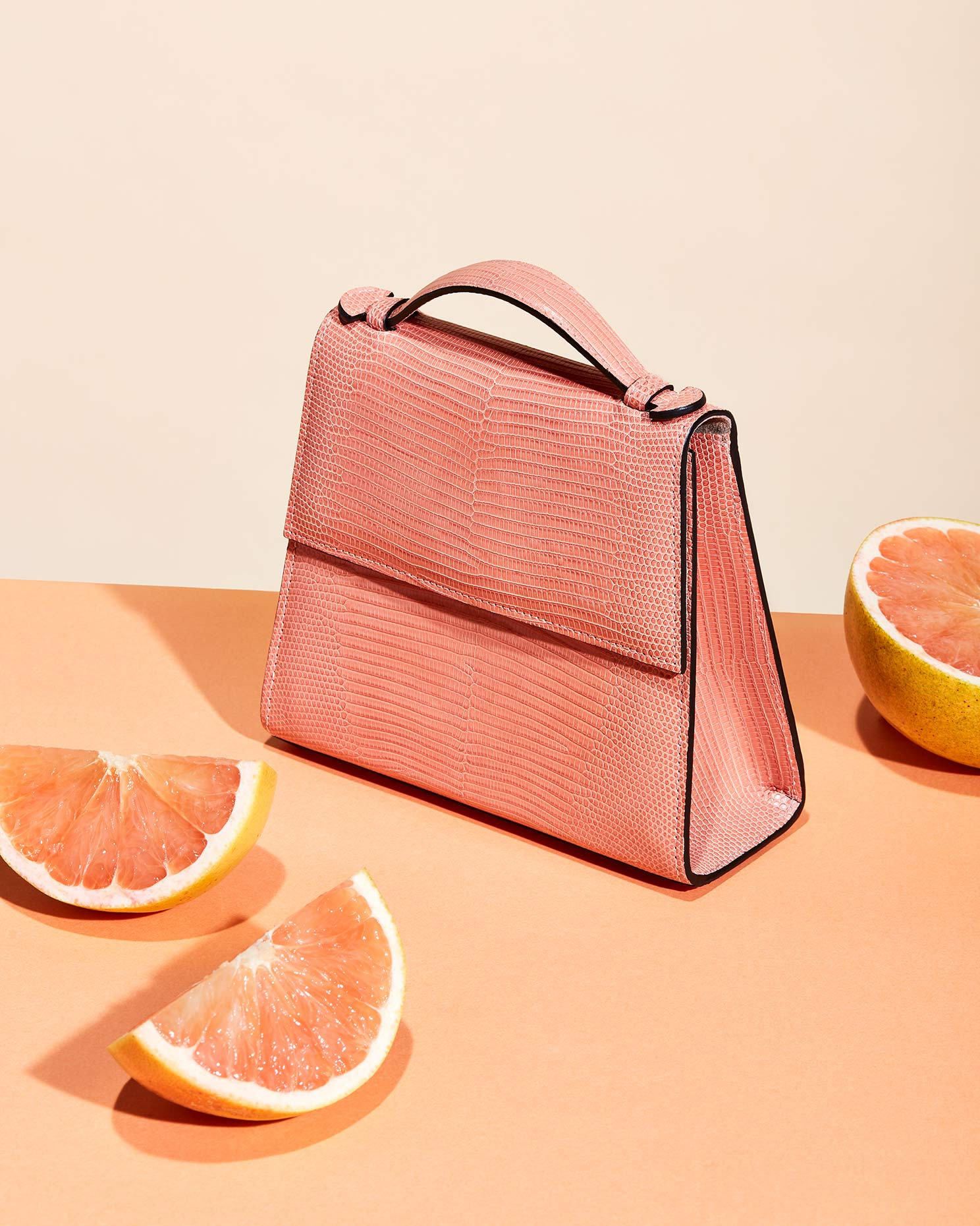 fashion accessory photograph featuring a pink handbag and grapefruit sections.