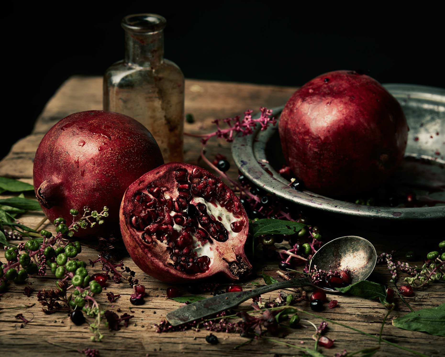 Still life photography featuring a pomegranate and metal dishes.