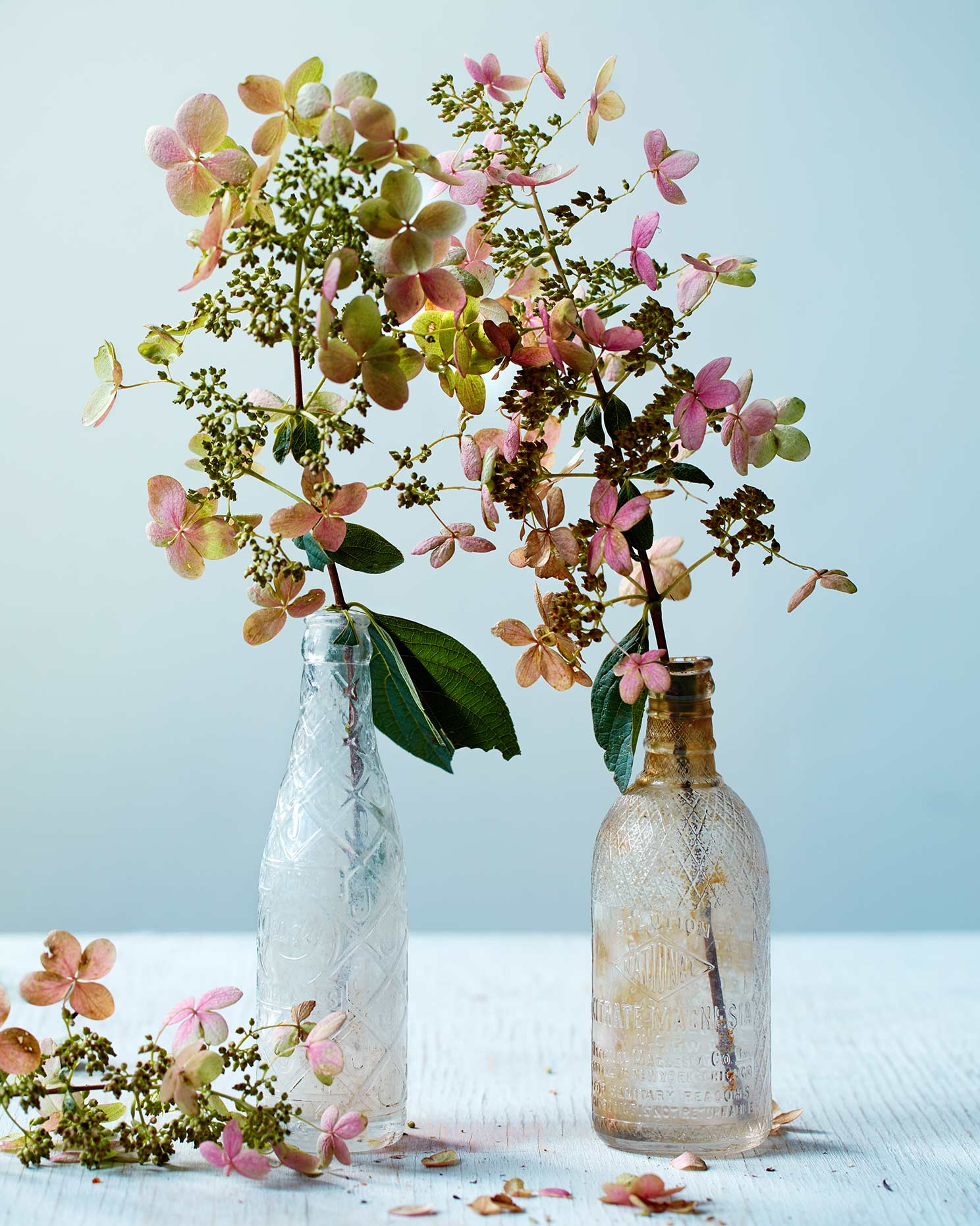 Old colorful flowers in antique bottles.