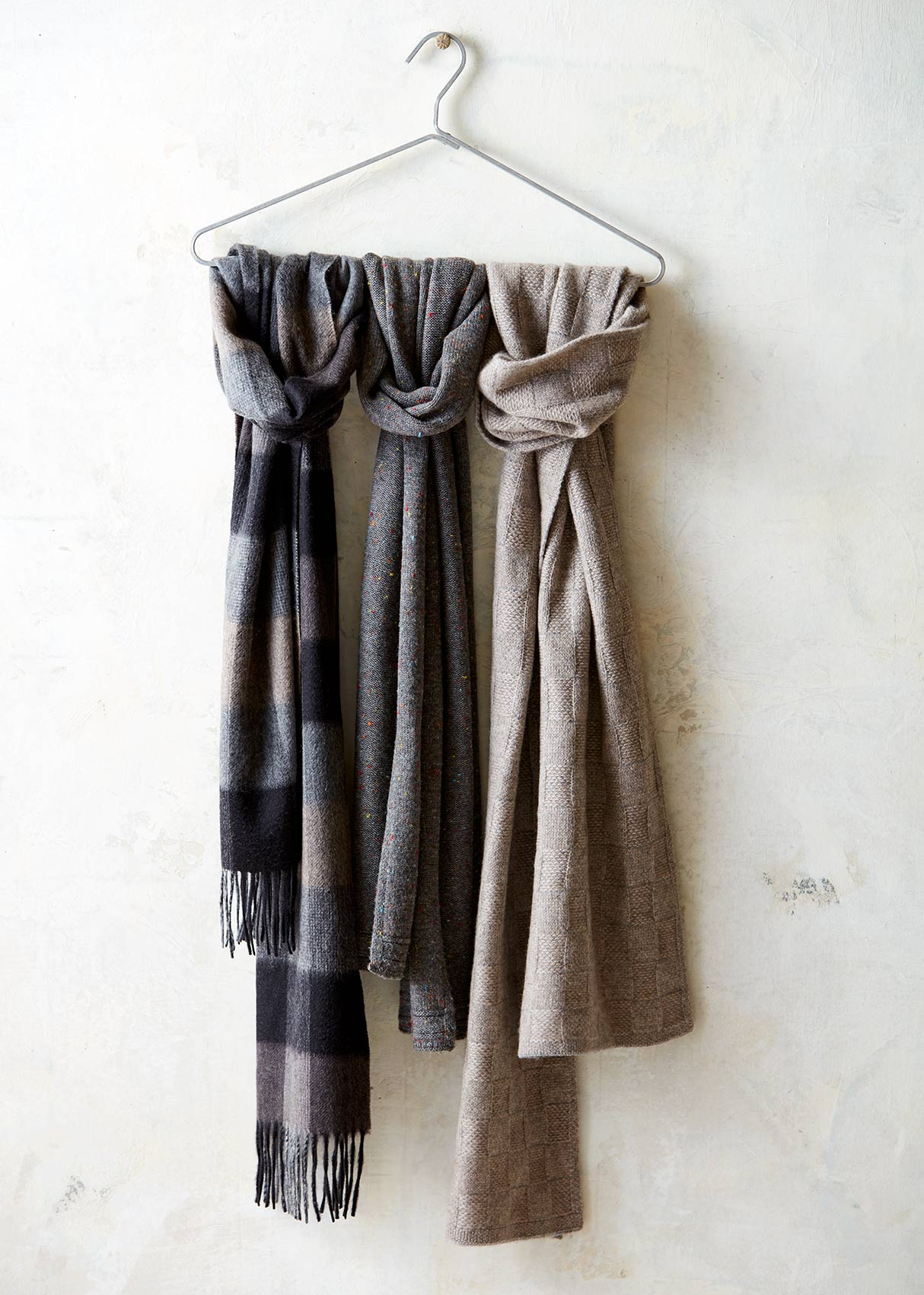 Catalog photography featuring scarves hung against a plaster wall