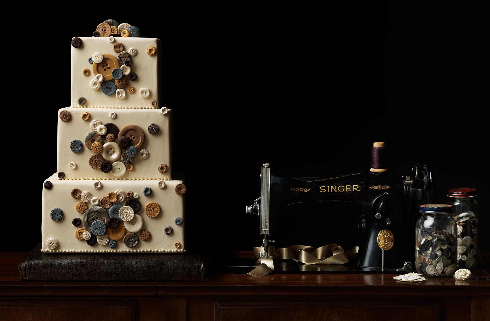 Button wedding cake photograph with a vintage sewing machine.
