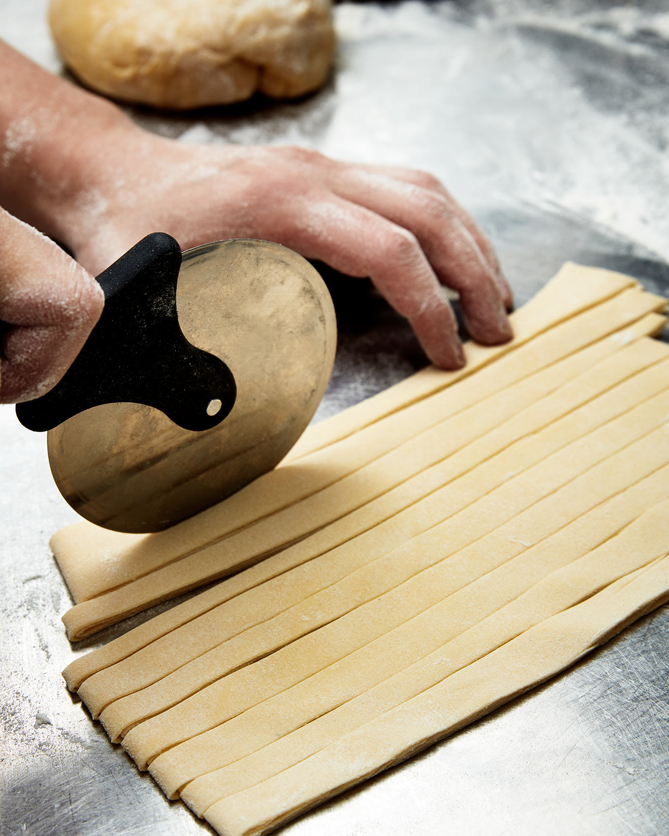 A chef hands cuts pasta for his restaurant