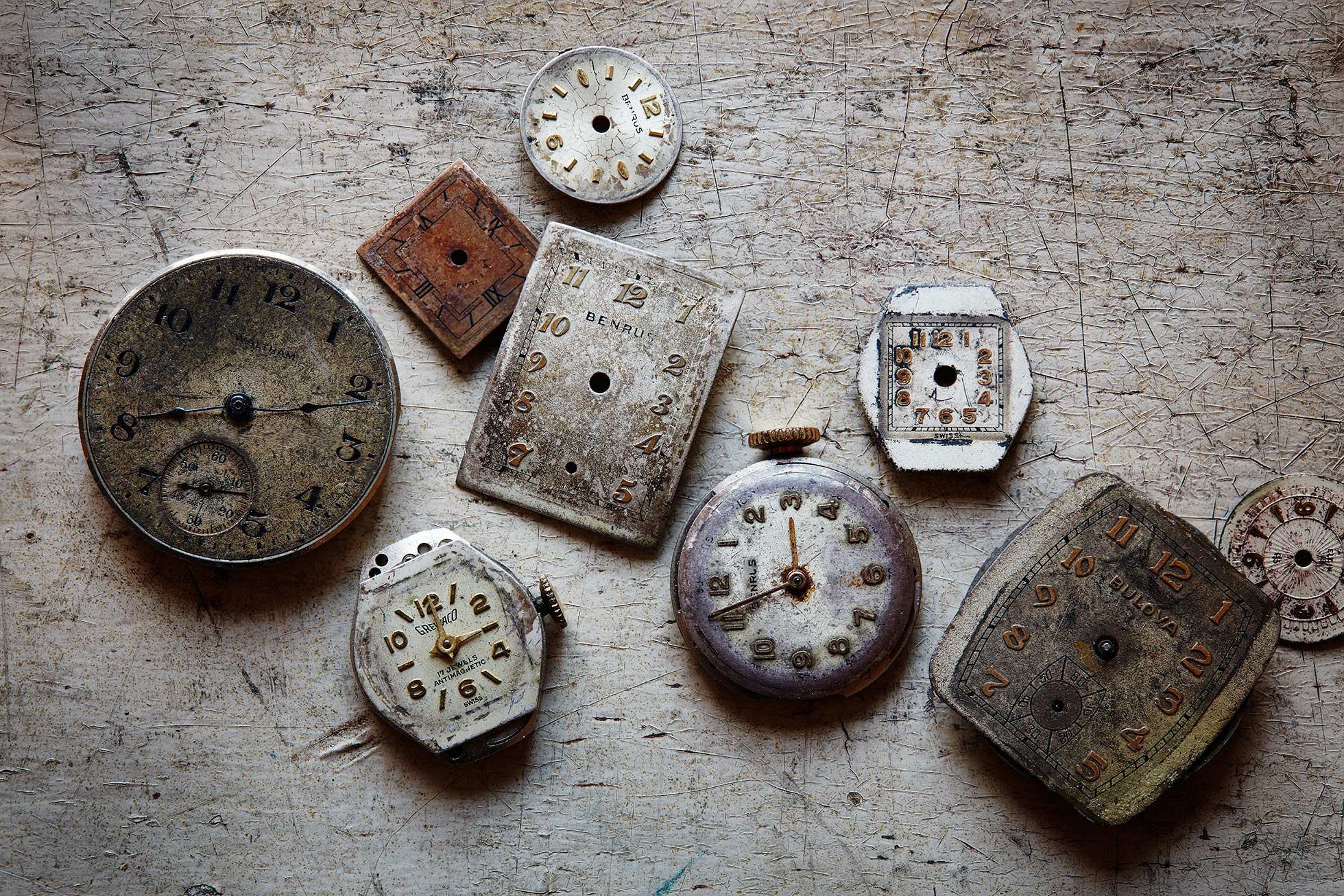 Various old watch faces on a rustic background.