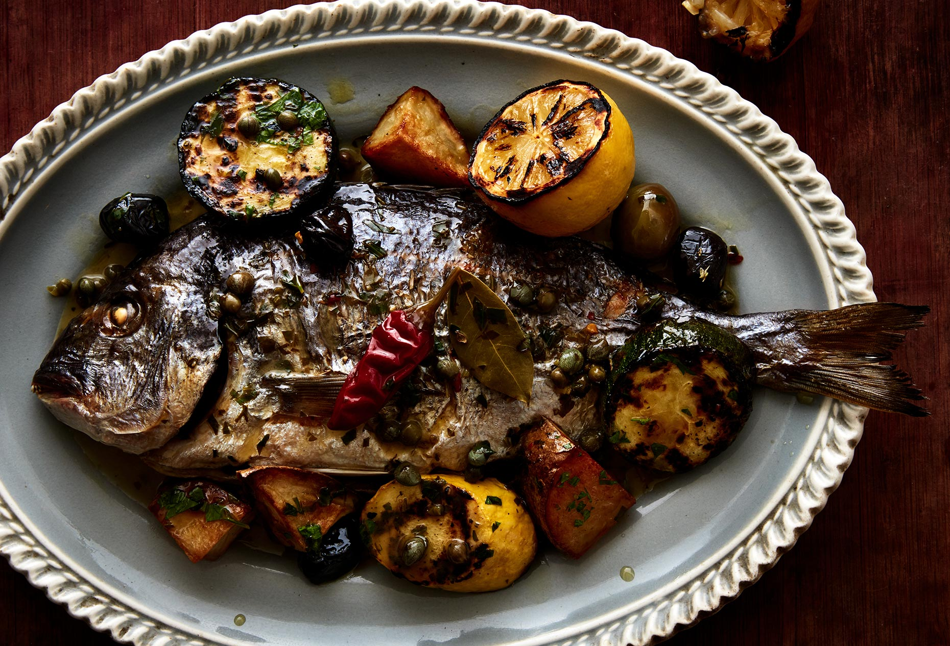 Whole roasted fish on a plate with lemons and vegetables.