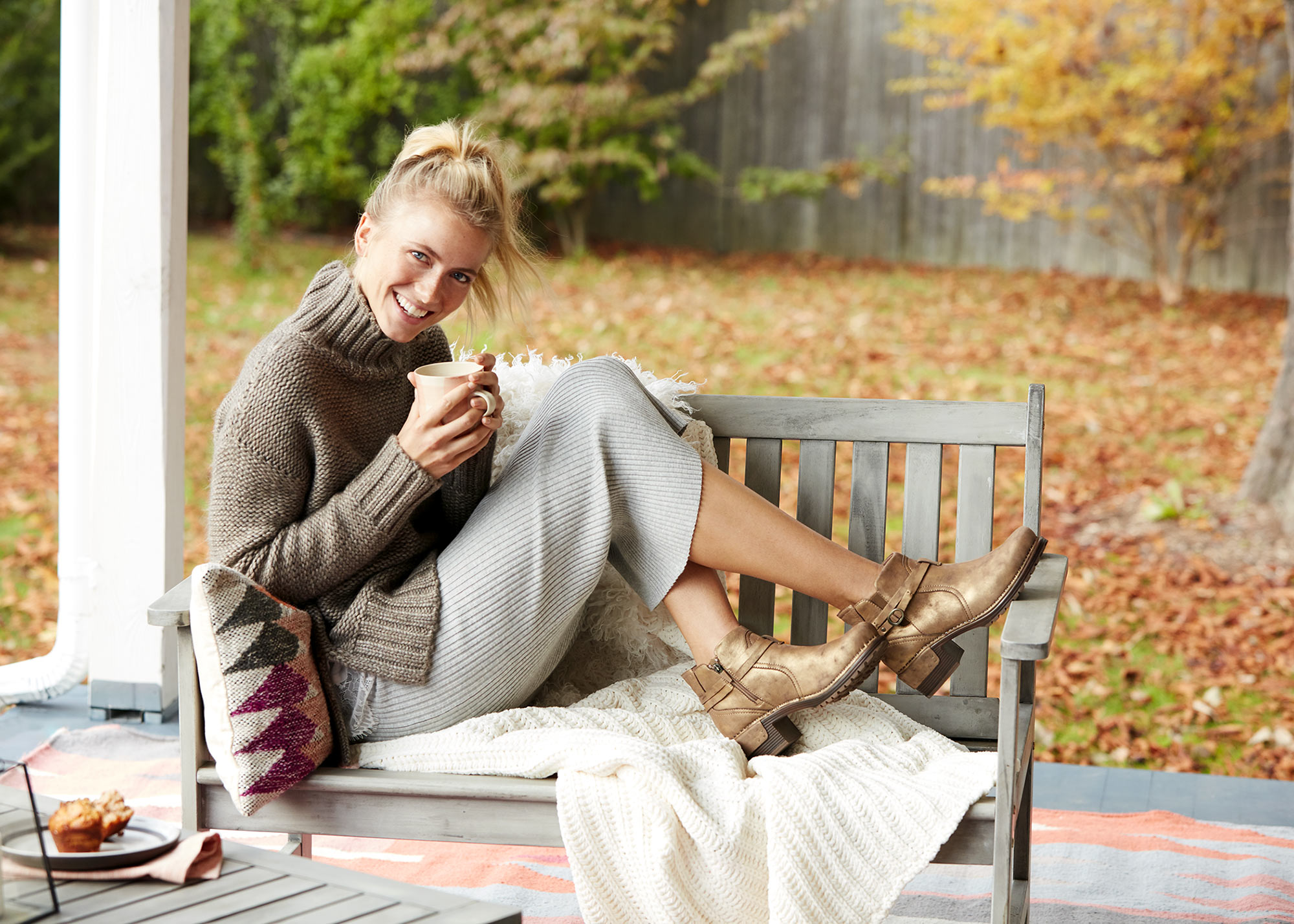 A young woman sitting on her porch enjoying coffee