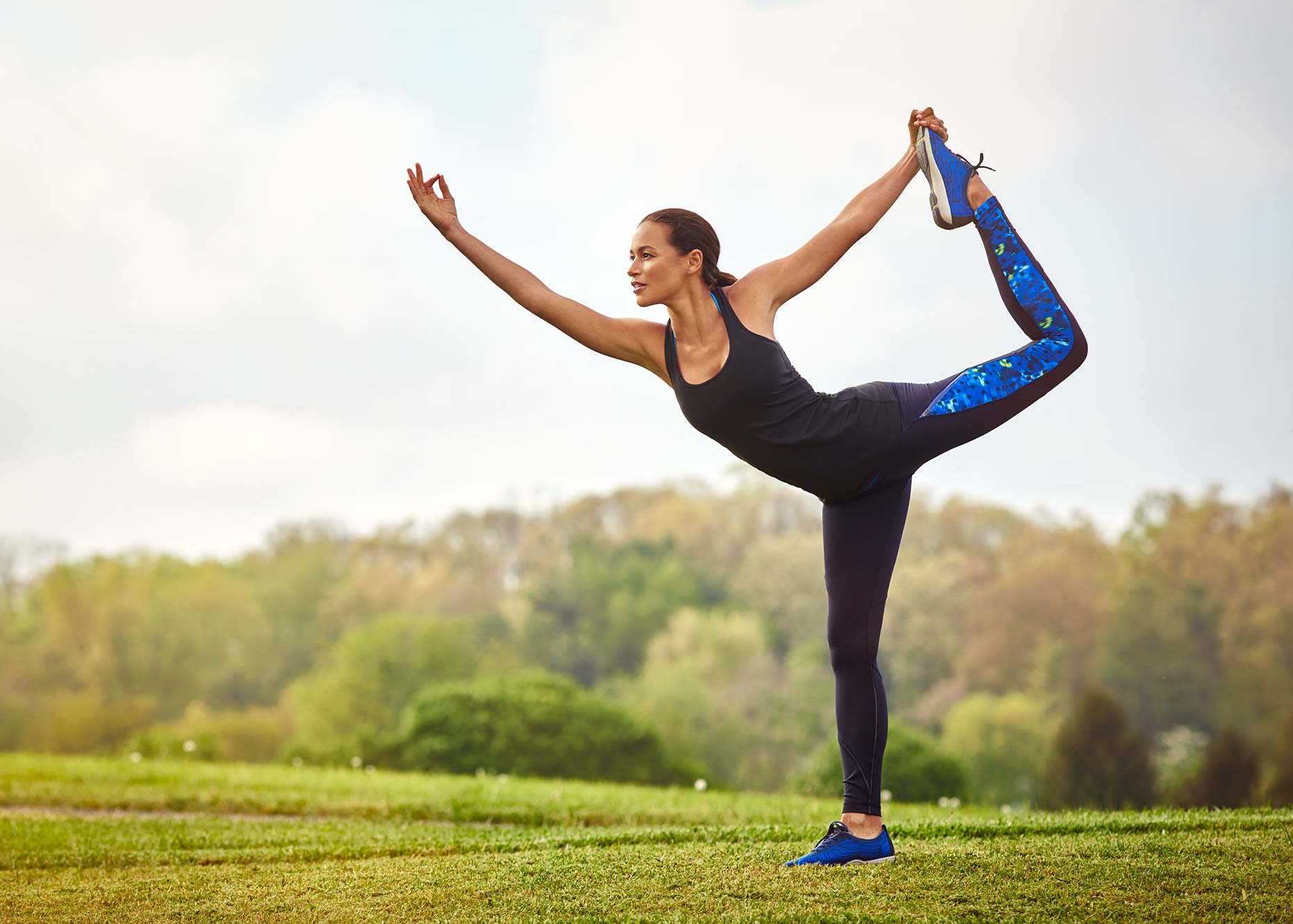 A woman does a yoga pose on a beautiful hillside
